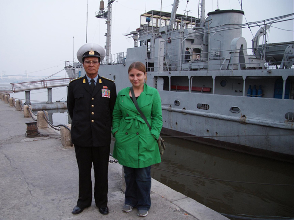 Tanya standing with a North Korean soldier in front of the captured spy ship USS Pueblo